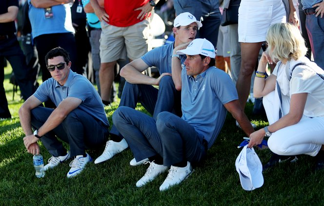 Europe's Rory McIlroy, Thomas Pieters and Rafael Cabrera-Bello look dejected as they watch on during the singles matches on day three of the 41st Ryder Cup at Hazeltine National Golf Club in Chaska, Minnesota, USA.