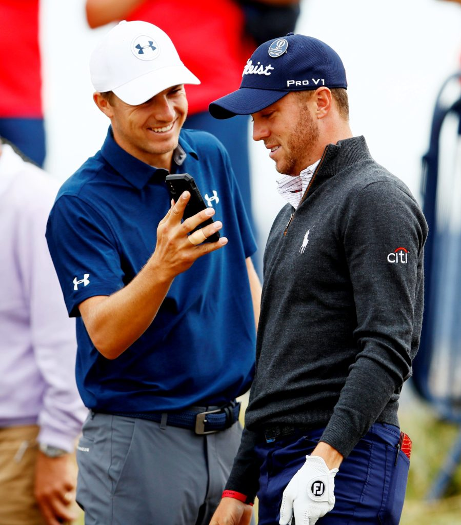 Golf - The 147th Open Championship - Carnoustie, Britain - July 17, 2018 Jordan Spieth of the U.S. shows his phone to Justin Thomas of the U.S. during the practice round REUTERS/Jason Cairnduff