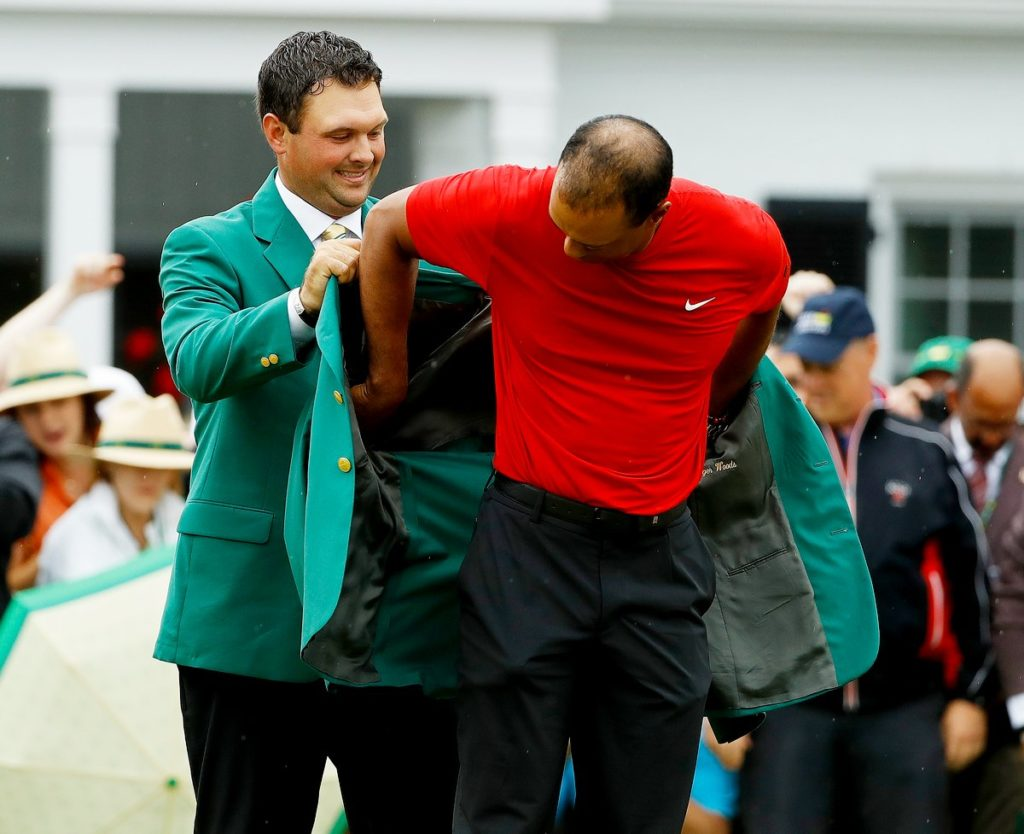 Patrick Reed, the 2018 Masters champions, helps Tiger Woods with his green jacket